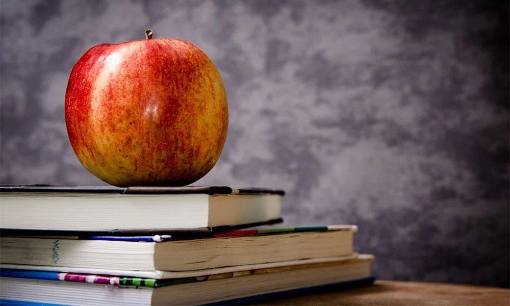 An apple sits atop three books
